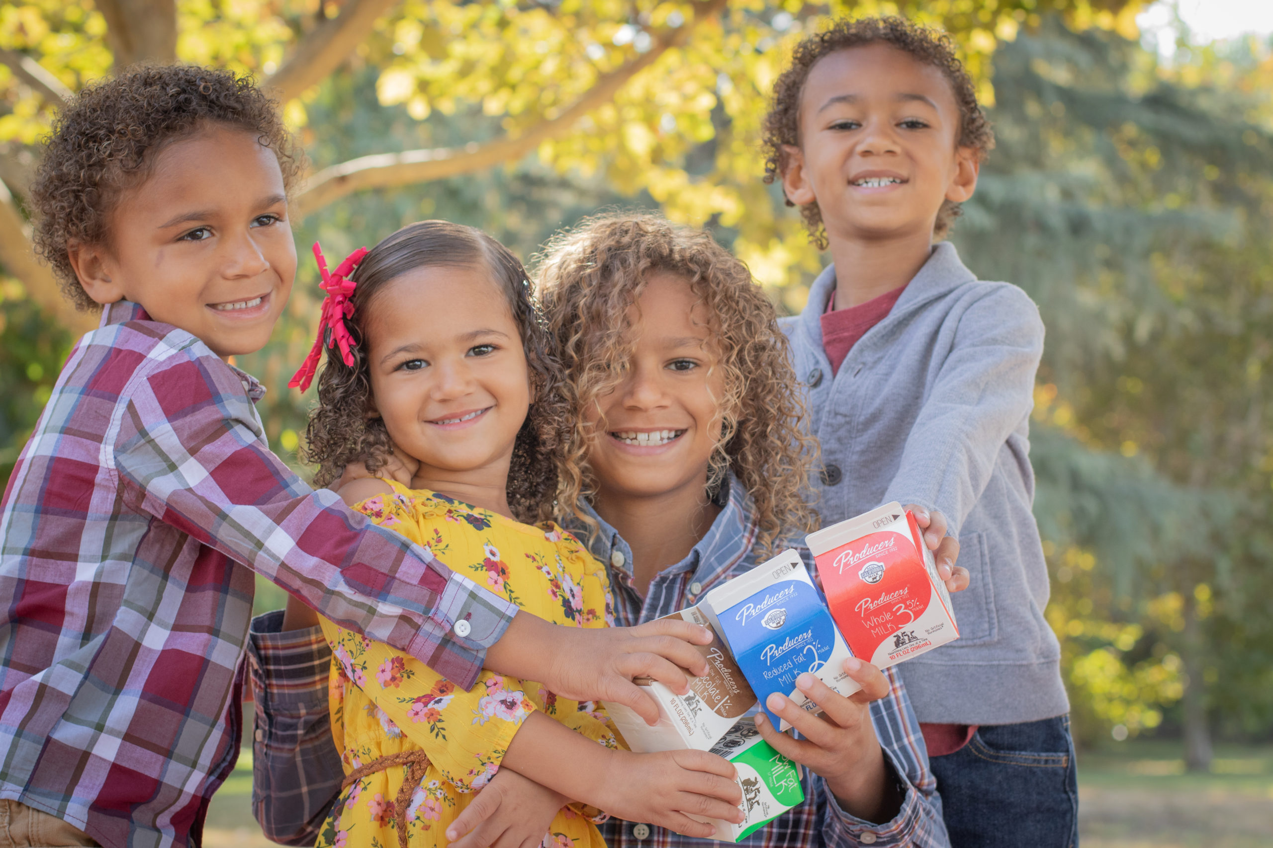 4 kids holding producers milk in the park.